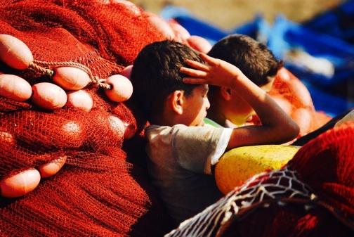 Bambini seduti al sole, tra le reti da pesca, ad Essaouira    JustReadTheWorld©